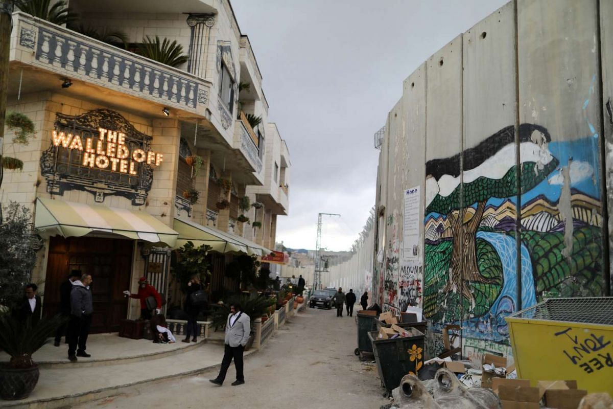 People stand outside the Walled-Off Hotel, which was opened by street artist Banksy, in the West Bank city of Bethlehem on March 3, 2017.