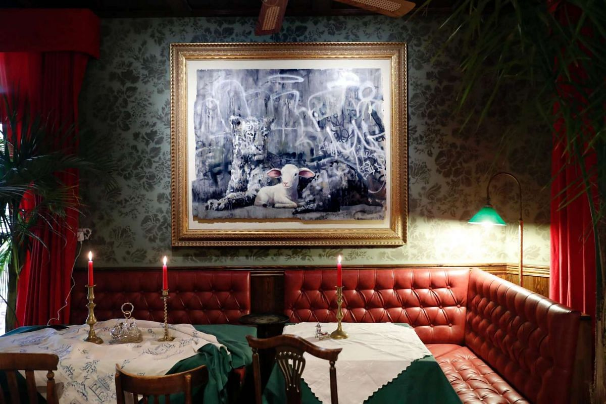 A Banksy installation hangs above the booths in the hotel lobby.