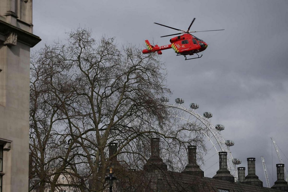 An air ambulance flies above Portcullis House, next to the Houses of Parliament in central London on March 22, 2017.