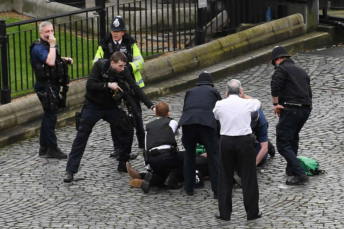 A policeman points a gun at a man, believed to be the attacker, on the ground as emergency services attend to the scene outside the Palace of Westminster, London, on March 22, 2017.