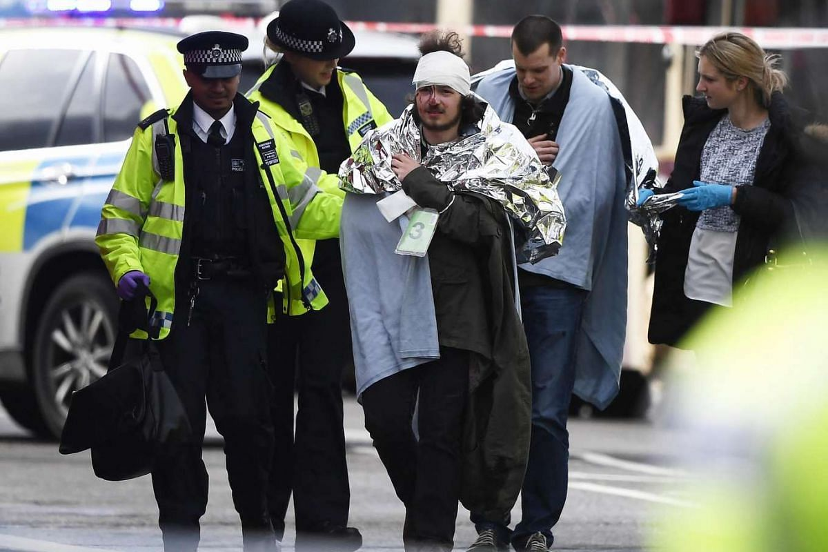 A member of the public is treated by emergency services near Westminster Bridge and the Houses of Parliament on March 22, 2017.