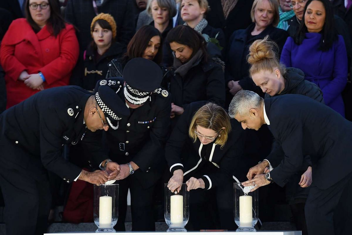 (From left to right) British Deputy Police Commissioner Craig Mackey, Home Secretary Amber Rudd and London Mayor Sadiq Khan lighting candles during a vigil in Trafalgar Square in London, Britain, on March 23, 2017.