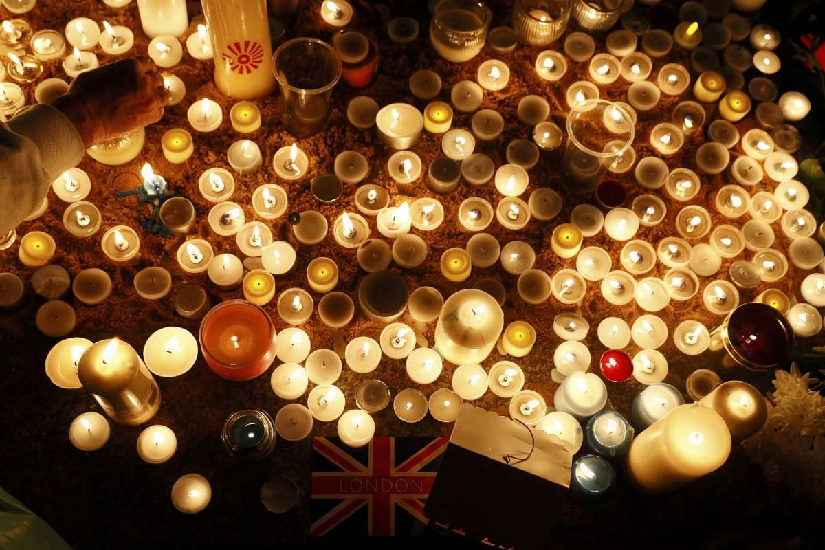 People lighting candles at a vigil in Trafalgar Square the day after an attack, in London, Britain, on March 23, 2017.