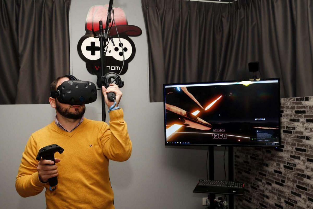 Mr Robert Majzik, 36, playing virtual-reality game Space Pirate Trainer at V-Room.