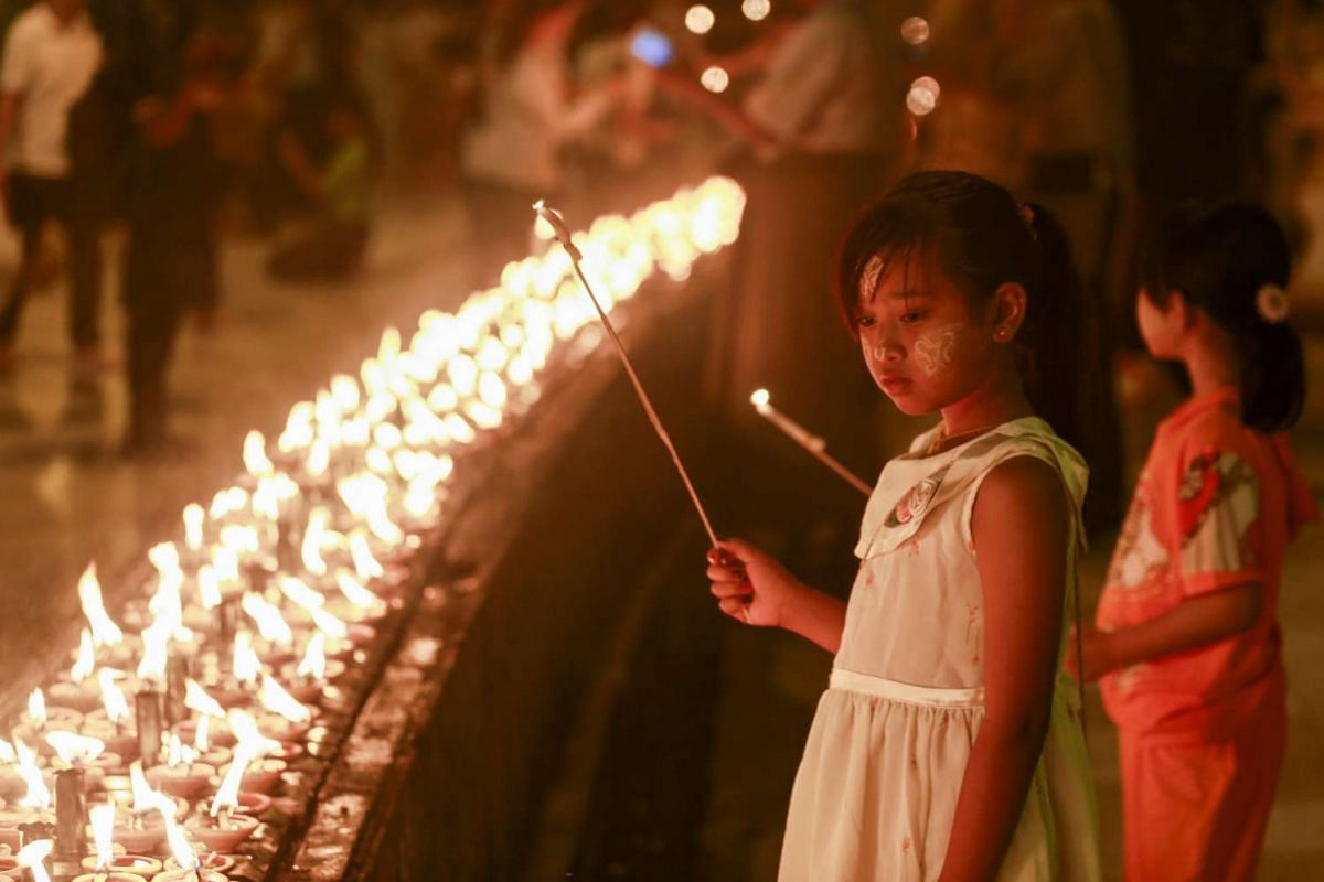 A girl wearing Thanakha, a yellowish-white traditional cosmetic paste, lights up the oil lamps at holy Shwedagon pagoda as part of Myanmar's first ever Earth Hour commemoration.