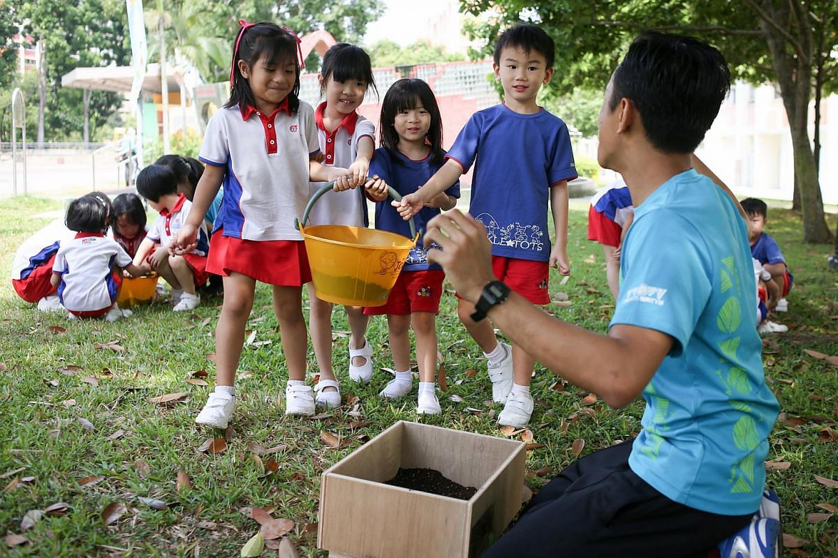 """Children from a PCF Sparkletots Preschool @ Tampines Central Blk 858 carrying a bucket of soil that they have loosened using their hands. They will then plant wheatgrass seeds and water them together under the guidance of """"ranger"""" Yazid Jalil (right)"""