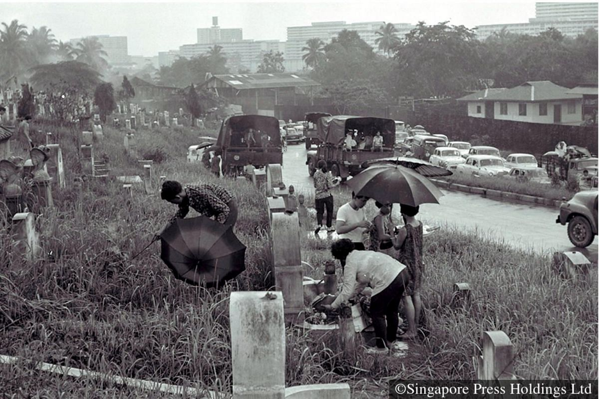 1970: Umbrellas pop open as shade from the rain as families pay homage to the dead. Special arrangements like one-way traffic system would be made to ease traffic flow during Qing Ming.