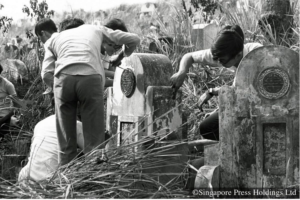 1974: Giving the final resting place of loved ones a good spring clean includes trimming overgrown grass around the grave or painting and fixing gravestones, as seen at this cemetery at Upper Serangoon Road.