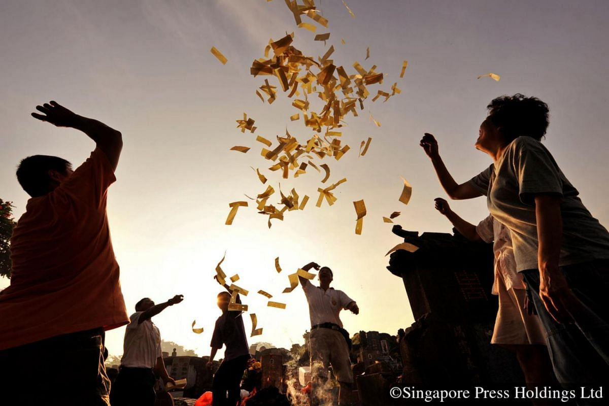 """2008: Shouts of """"Huat Ah!"""" (Dialect for """"to prosper"""") accompany the throwing of joss paper in the air as people ask for their ancestors' blessings at the Choa Chu Kang cemetery."""