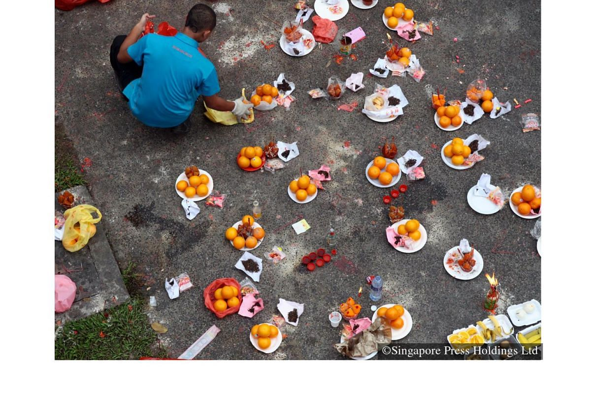 2013: A worker at the Mandai Crematorium and Columbarium Complex collects the fruit offerings left behind from Qing Ming prayers.