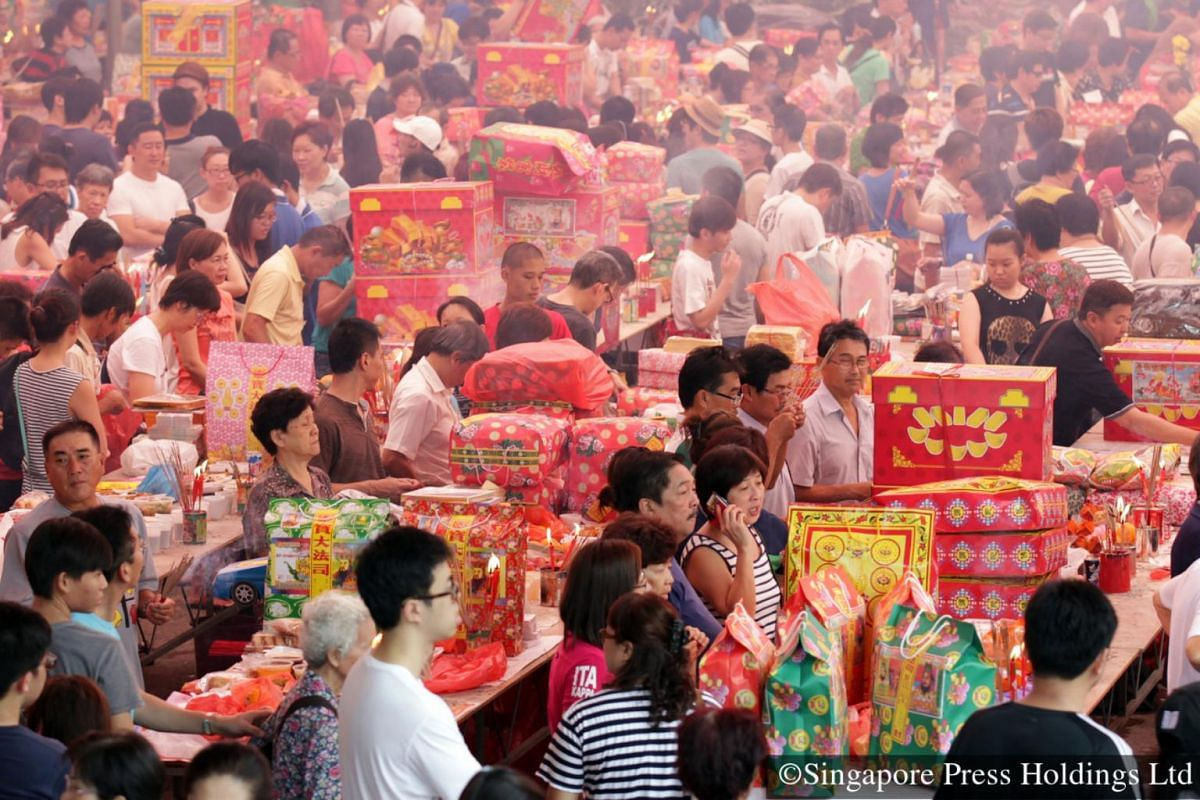 2014: The whole family gets involved as paper 'gifts' are arranged in piles before being lit as offerings to ancestors.