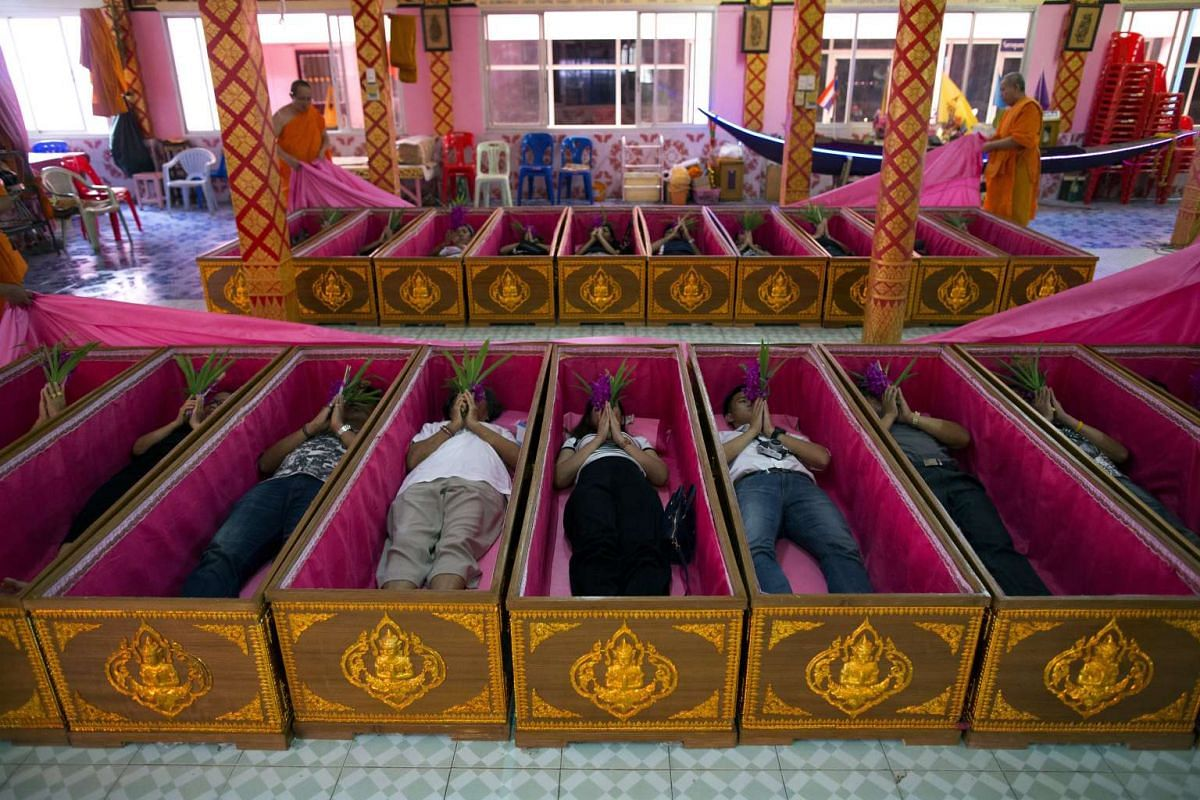 Thai devotees lie inside coffins as Buddhist monks officiate during a coffin ritual at Wat Takien Temple in Nonthaburi province, Thailand, 01 April 2017.