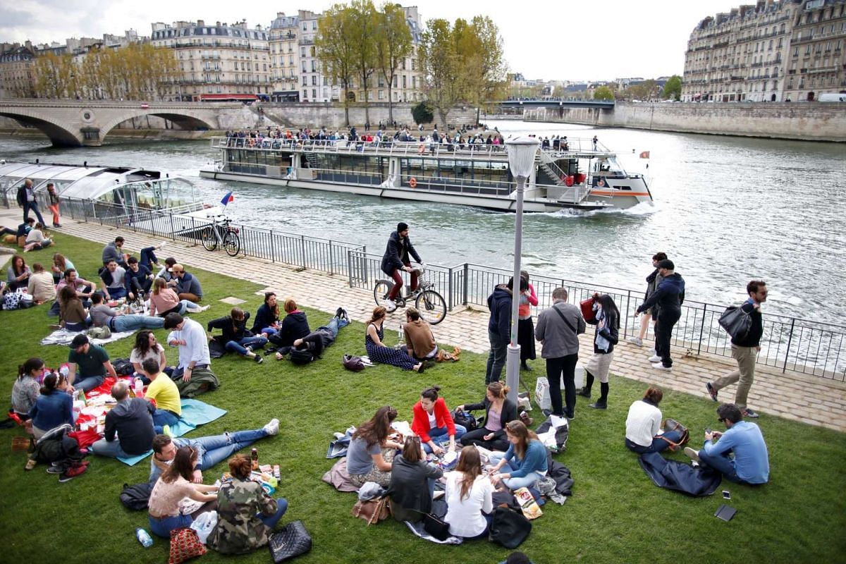 """People enjoy the good weather on the bank of the river Seine during the inauguration of the """"Rives de Seine"""" Park in Paris, France, April 2, 2017."""