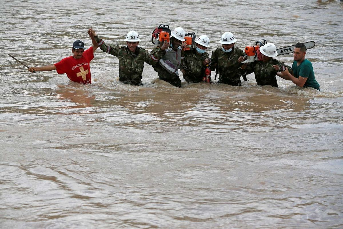 Rescuers walk in the river with chainsaws after heavy rain caused flooding and mudslides in Mocoa, Colombia, April 2, 2017.