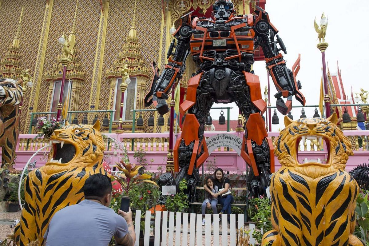 A Thai family takes photos with a large statue of a character from the movie Transformers at Wat Takien Temple, Nonthaburi province, Thailand, April 1, 2017. (issued 03 April 2017).