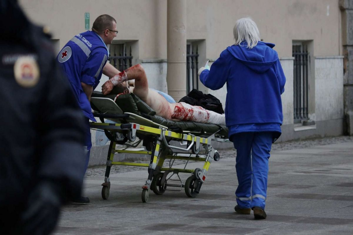 An injured person is helped by emergency services officers outside the Sennaya Ploshchad metro station in St Petersburg.