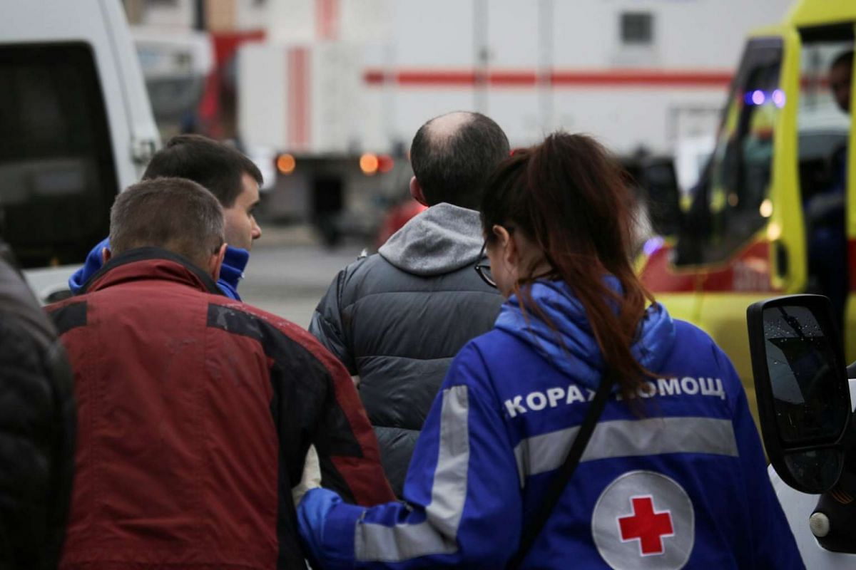 An injured person is helped by emergency services officers outside the Sennaya Ploshchad metro station on April 3, 2017.