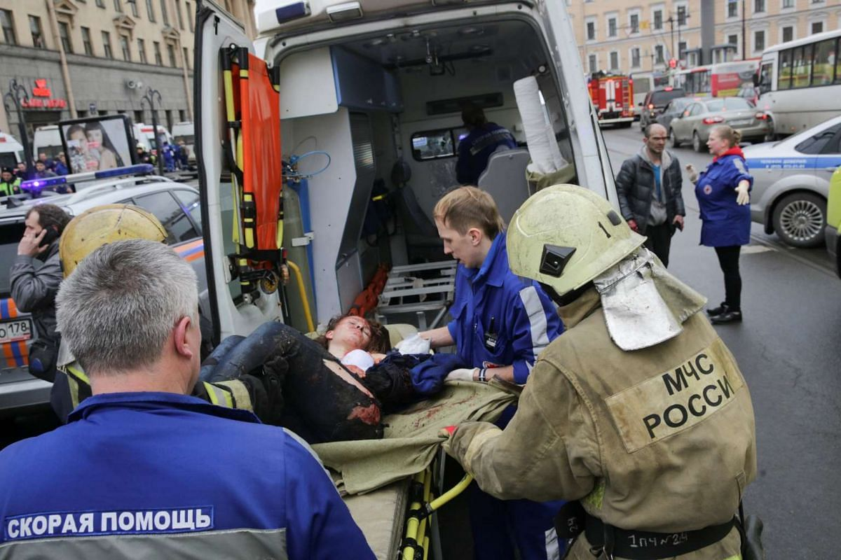 An injured woman is helped by emergency services officers outside the Sennaya Ploshchad metro station on April 3, 2017.