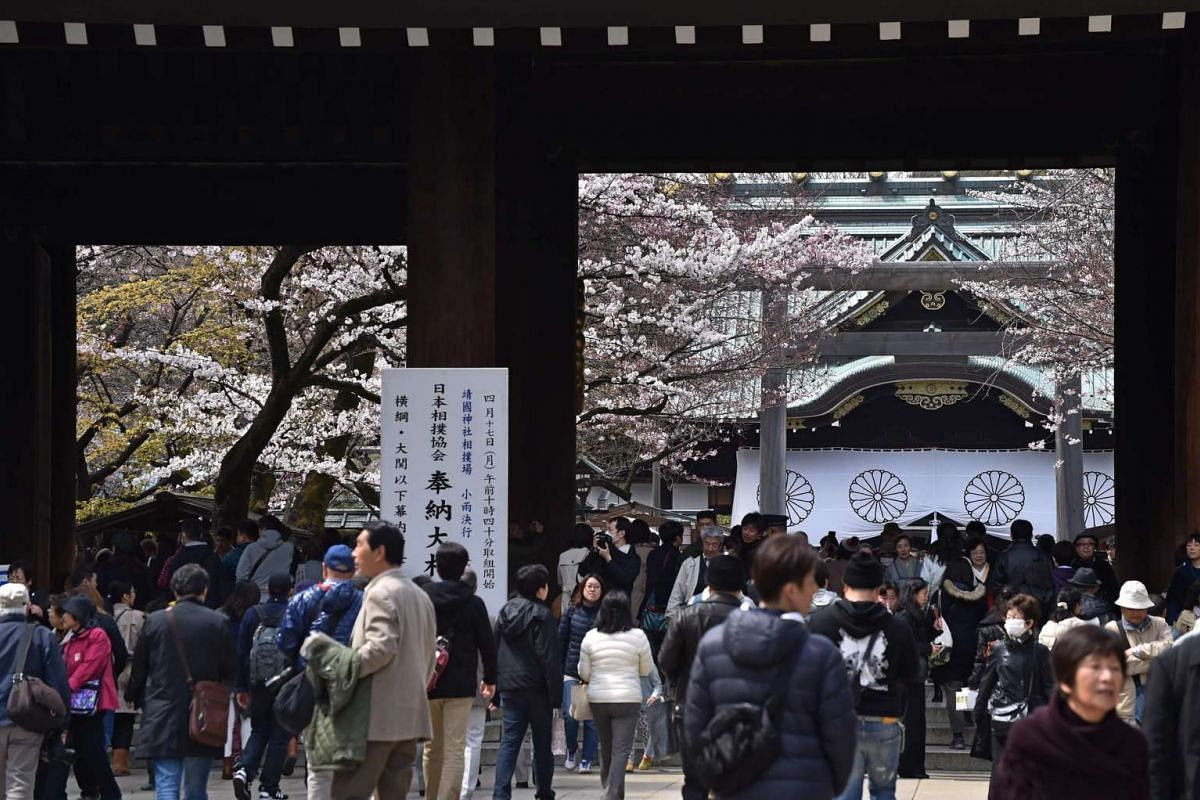 People visiting the Yasukuni Shine surrounded by full-bloom cherry blossoms in Tokyo on April 2, 2017.