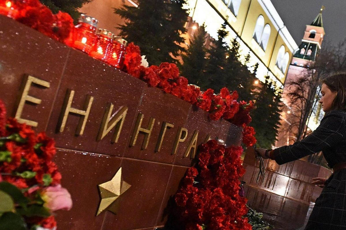 A woman laying flowers in memory of victims of the blast in the St Petersburg metro at a memorial stone reading Leningrad by the Kremlin wall in central Moscow, on April 3, 2017.