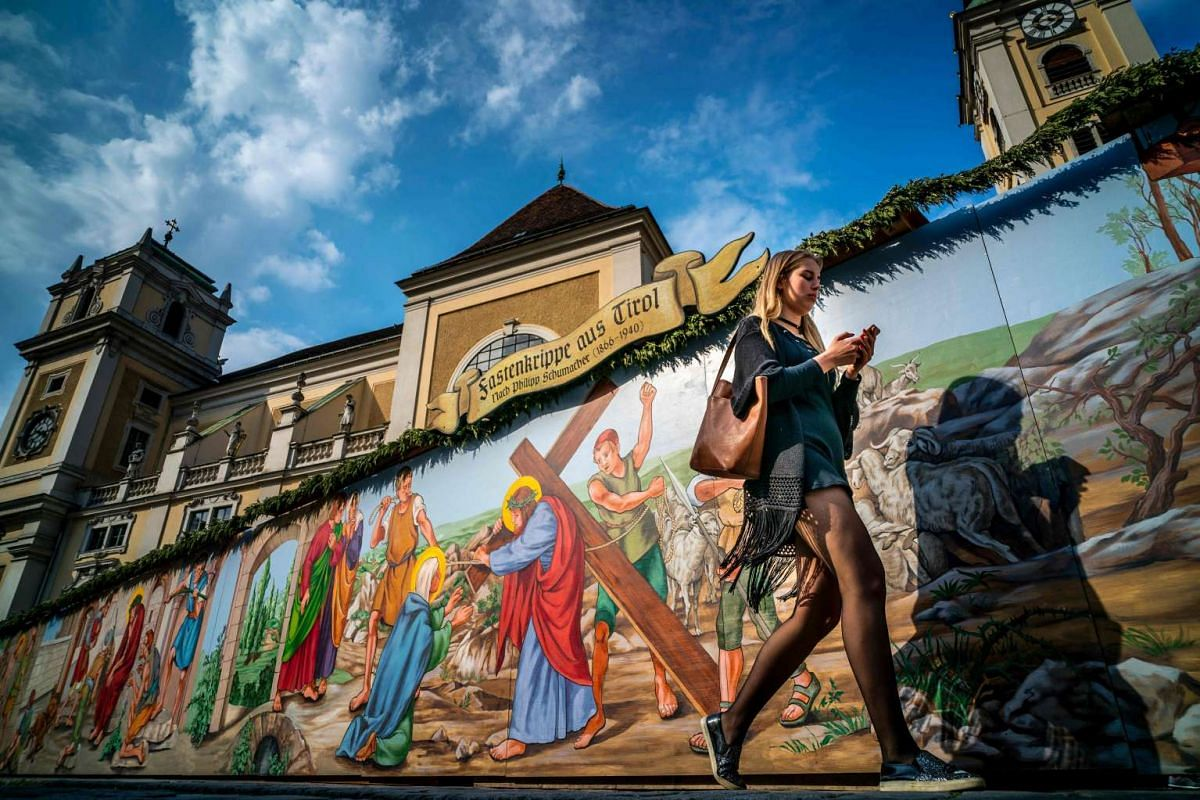 A woman walking past a mural depicting the Biblical Easter story at the Easter Freayung market in Vienna, Austria, 10 days before Easter, on April 4, 2017.