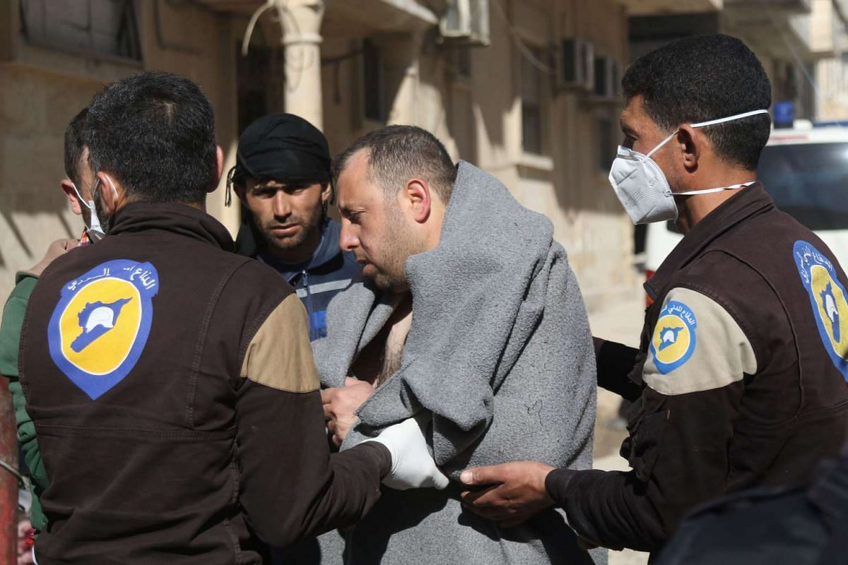 A Syrian man is taken by civil defence workers to a small hospital in the town of Maaret al-Noman.