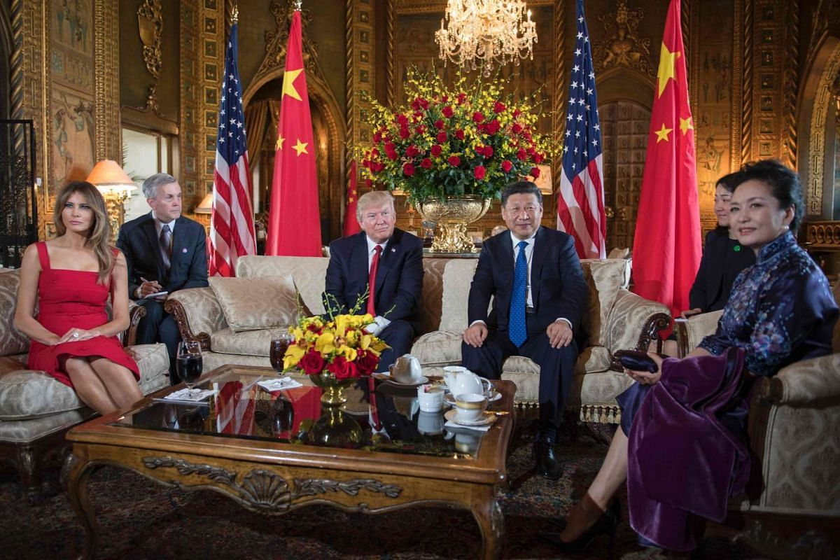 US President Donald Trump and First Lady Melania Trump posing for photos with Chinese President Xi Jinping (third from right) and first lady Peng Liyuan (right) in the living room of the Mar-a-Lago estate in Palm Beach, Florida on April 6, 2017.