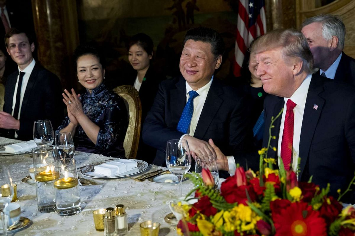 US President Donald Trump and Chinese President Xi Jinping shaking hands during a dinner at Mr Trump's Mar-a-Lago resort, on April, 6, 2017, watched by Mr Trump's senior adviser Jared Kushner and China's First Lady Peng Liyuan.