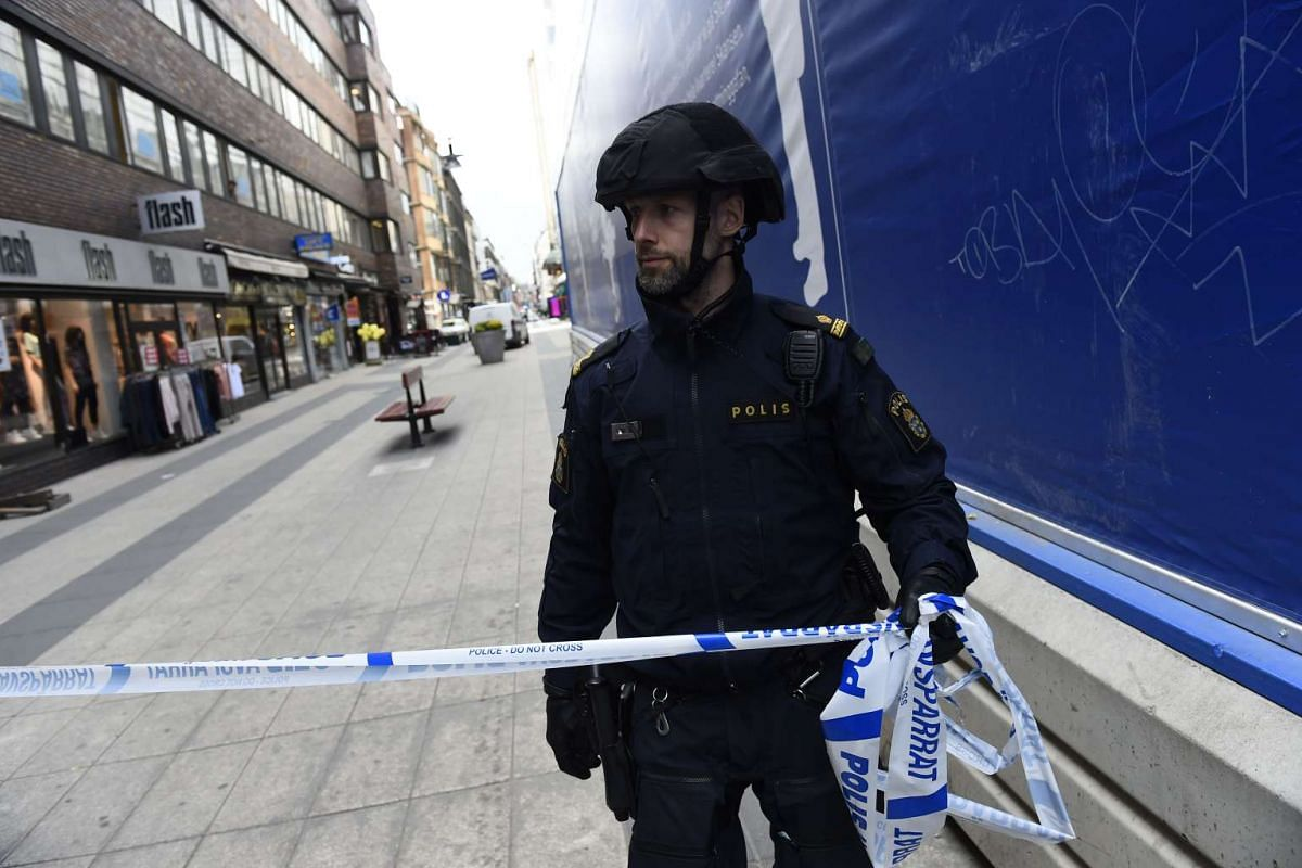 A policeman cordons the site where a truck crashed into a department store.