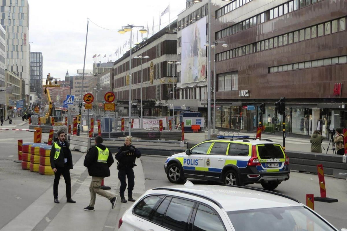 Police officers guard downtown Stockholm near the scene of the crash.