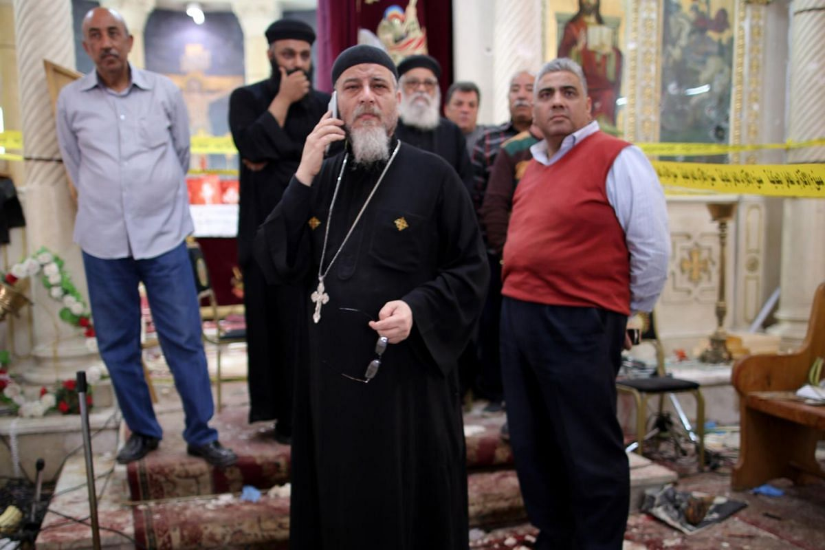 A Coptic priest stands next to security personnel investigating the explosion.