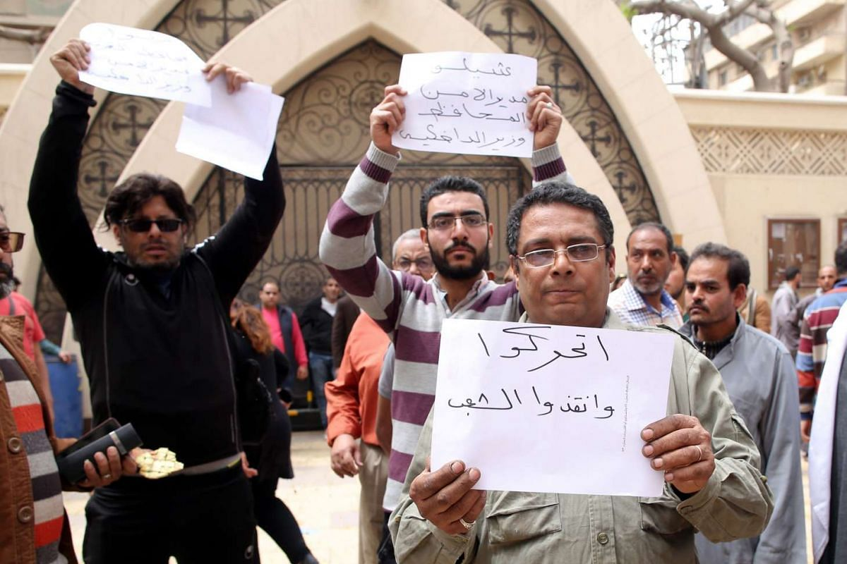 People hold signs protesting against the Egyptian Interior Minister outside the church.