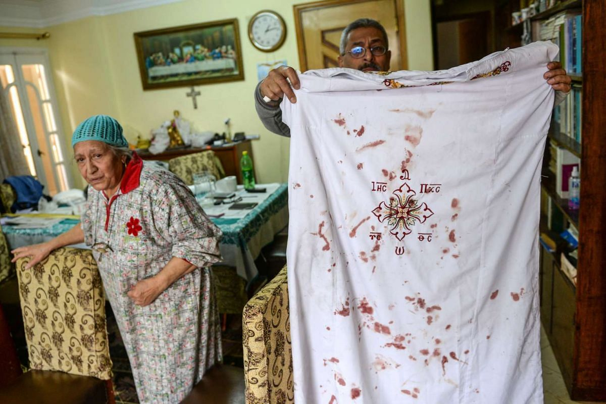 A man holds Coptic clergy clothes with bloodstains from the attack.