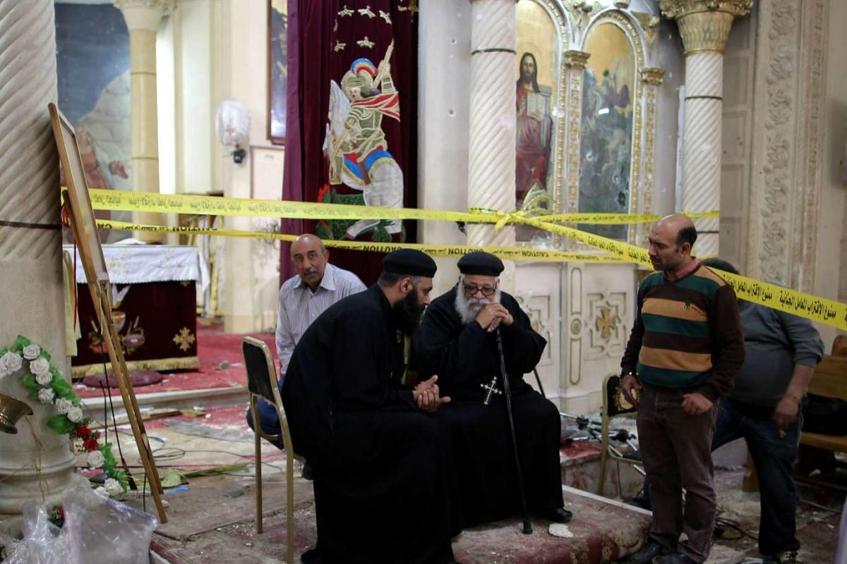 Coptic priests sit amid the damage caused by the explosion.
