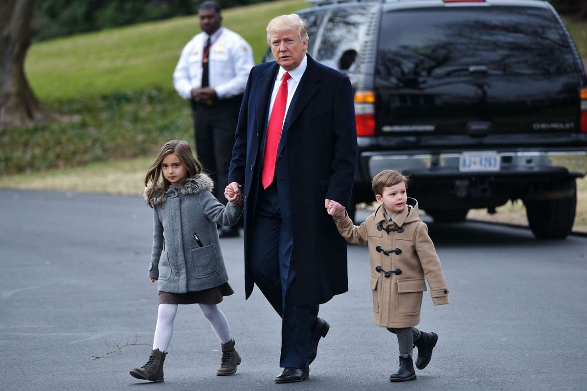 US President Donald Trump walks with grandchildren Arabella Kushner (left) and Joseph Kushner to board Marine One from the South Lawn of the White House on February 17, 2017 in Washington, DC.