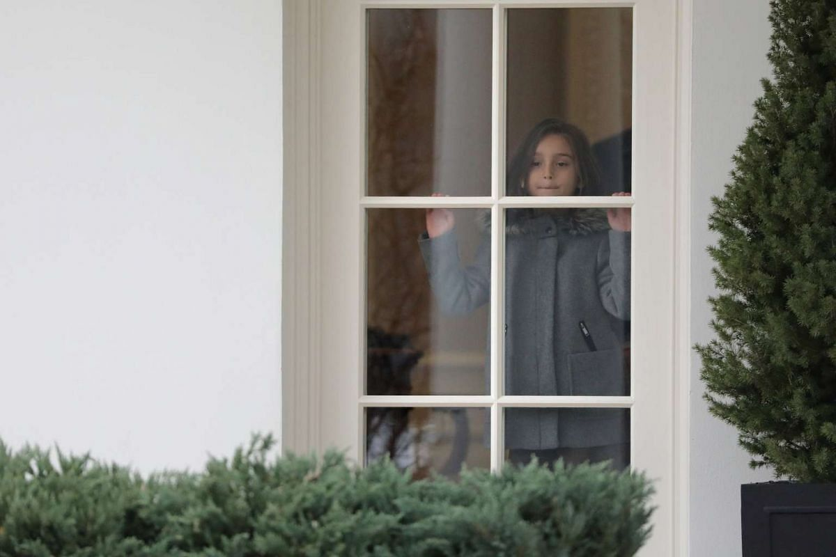 Arabella Kushner, granddaughter of US President Donald Trump, looks out the window from the Oval Office of the White House while the President prepares to depart Washington on February 17, 2017.