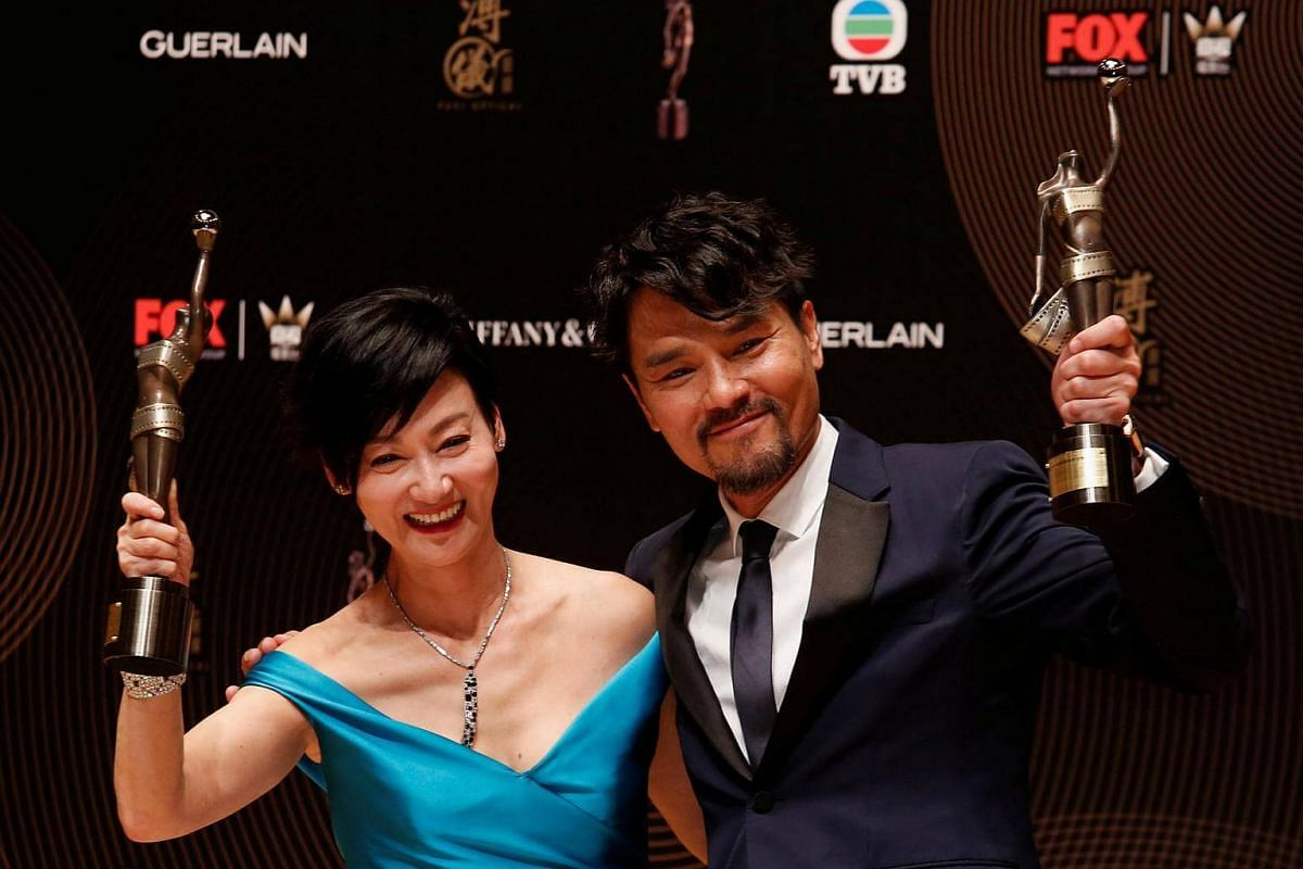 Hong Kong actor Gordon Lam and actress Kara Wai pose after winning the Best Actor and Best Actress awards for their roles in Trivisa and Happiness at the Hong Kong Film Awards on April 9, 2017.