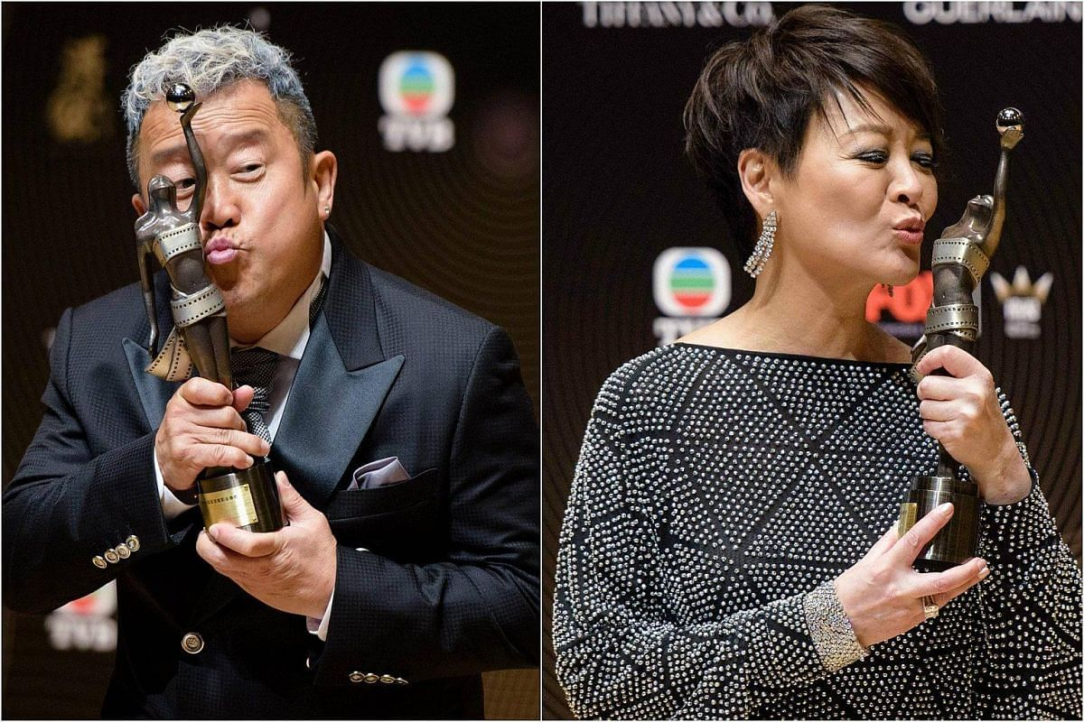 Hong Kong actor Eric Tsang and Taiwanese actress Elaine Jin celebrate after winning Best Supporting Actor and Actress awards at the Hong Kong Film Awards on April 9, 2017. Both won for their roles in Mad World.