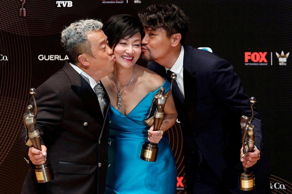 Best Supporting Actor Eric Tsang (left) and Best Actor Gordon Lam pose with Best Actress Kara Wai at the Hong Kong Film Awards on April 9, 2017.