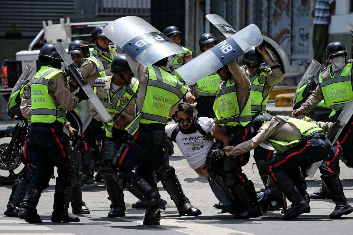 A demonstrator is arrested by riot police while rallying against Venezuela's President Nicolas Maduro's government in Caracas, Venezuela April 10, 2017. PHOTO: REUTERS