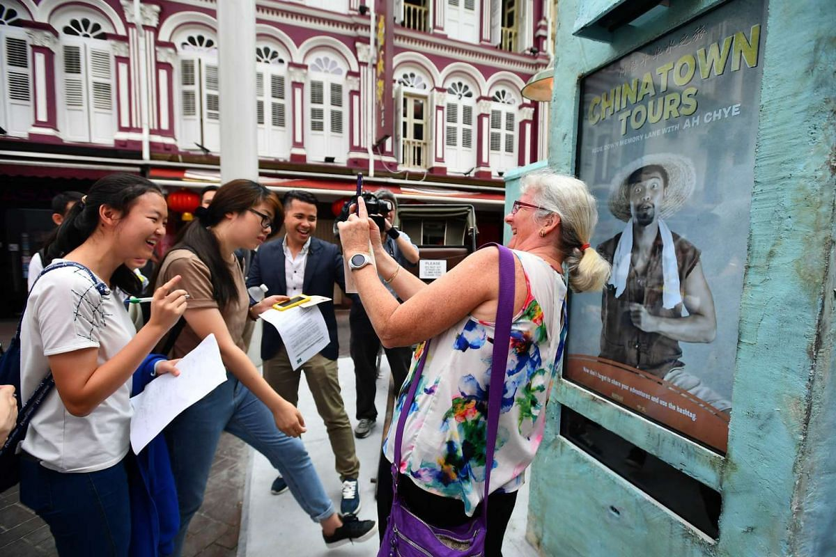Mrs Vicki Godden, a clerk and tourist from Australia, takes pictures with one of the characters embedded in an interactive digital screen installation at the Chinatown MRT, 10 April 2017. The characters make up Chinatown Comes Alive, a pilot initiati