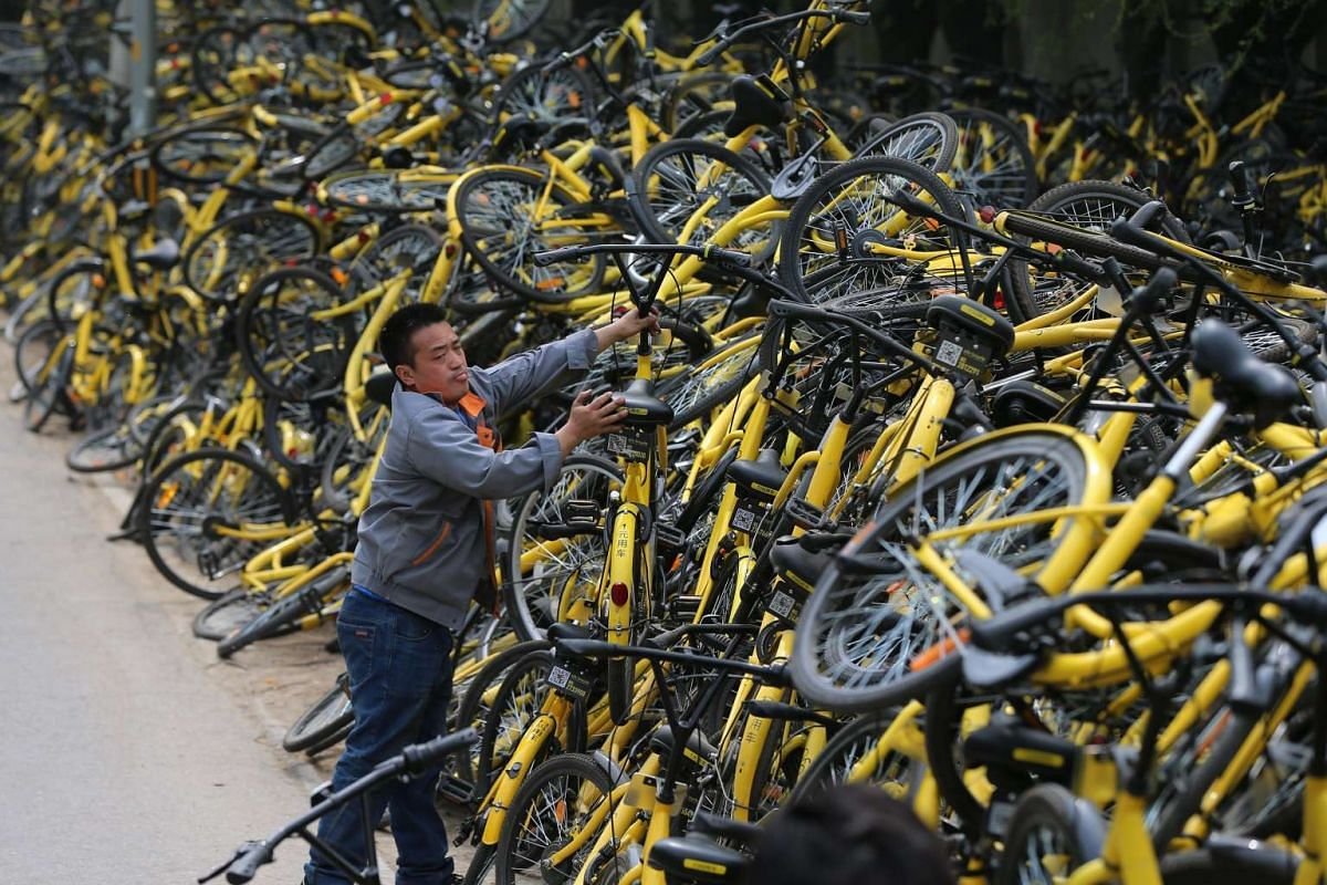 A Chinese mechanic carries a rental bicycle to place on top of other damaged bicycles at the rental bicycle company OFO a repair depot that collected tens thousand of damaged rental bicycle in Beijing, China, April 10, 2017. PHOTO: EPA
