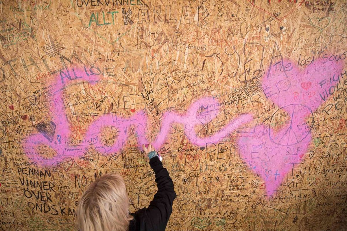 A woman sprays a graffiti on a plywood wall at a makeshift memorial to commemorate the victims of Friday's terror attack near the site where a truck drove into Ahlens department store in Stockholm, Sweden, on April 10, 2017. PHOTO: AFP
