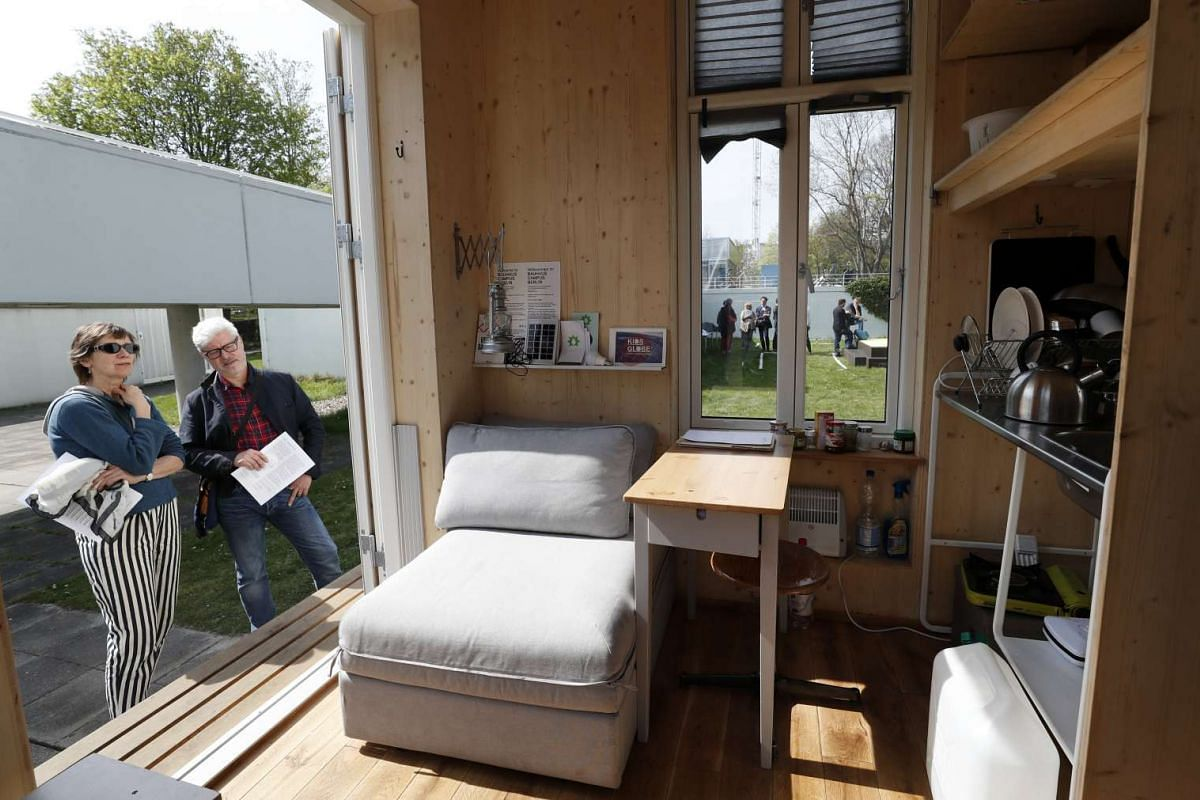 People look at the interior of a home unit, a small mobile living space, part of a project of the Tiny House University at the Bauhaus Archive Museum of Design in Berlin, Germany, April 10, 2017. PHOTO: EPA