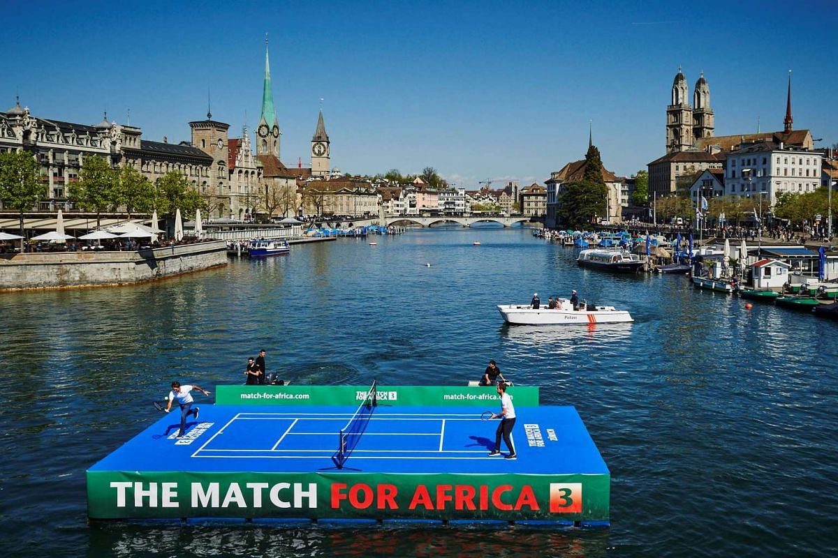 Swiss tennis superstar Roger Federer (L) returns a ball to world number one Britain's Andy Murray during a promotion on a raft on the river Limmat before a charity tennis match on April 10, 2017 in Zurich. PHOTO: AFP