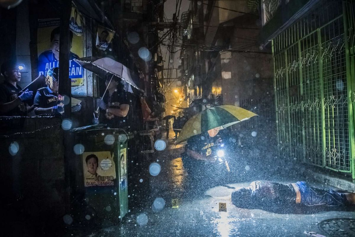Police investigators hunching over the body of Romeo Torres Fontanilla in Manila, Philippines, on Oct 11, 2016.