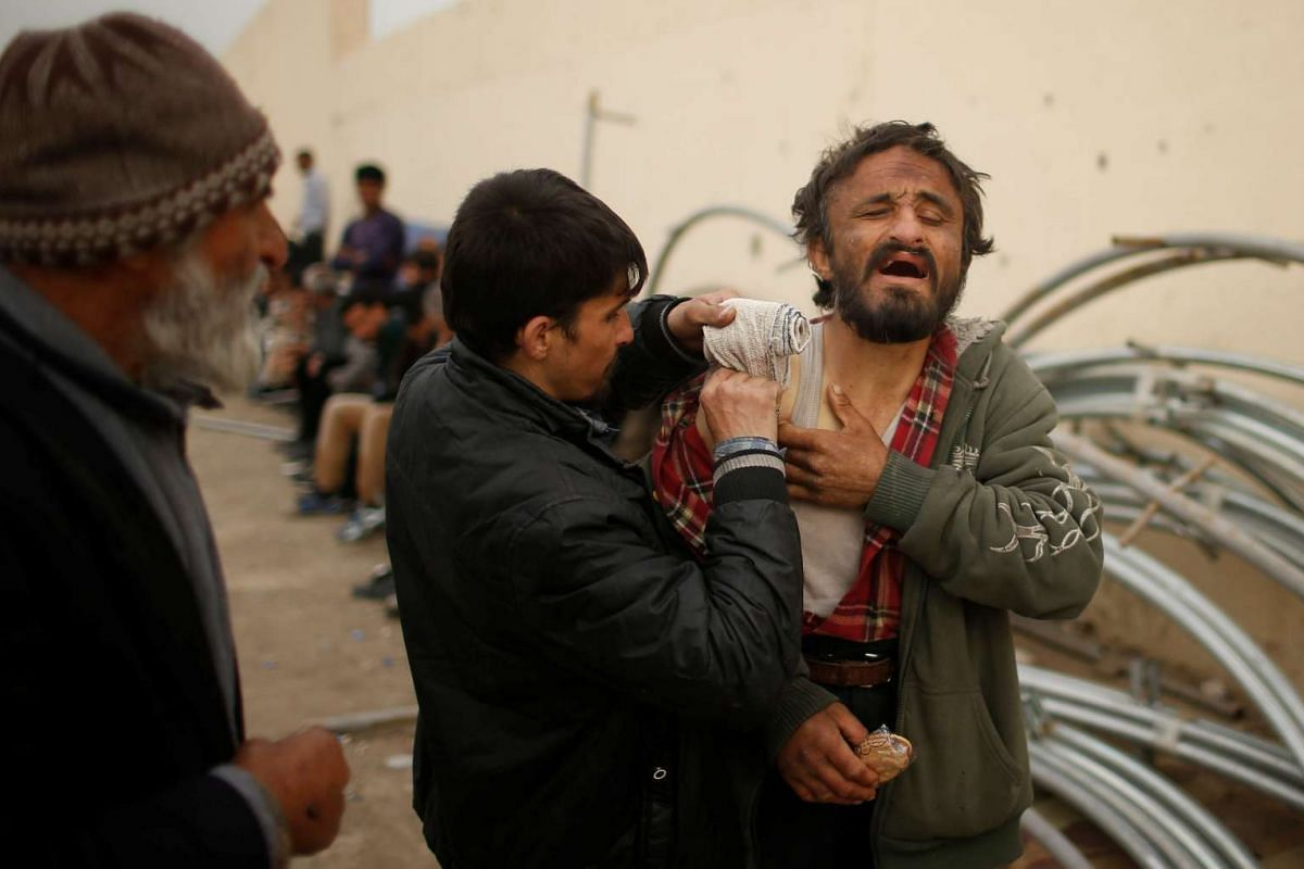 A displaced Iraqi who had fled his home helps his wounded brother as Iraqi forces battle with Islamic State militants, in western Mosul, Iraq April 11, 2017. PHOTO: REUTERS