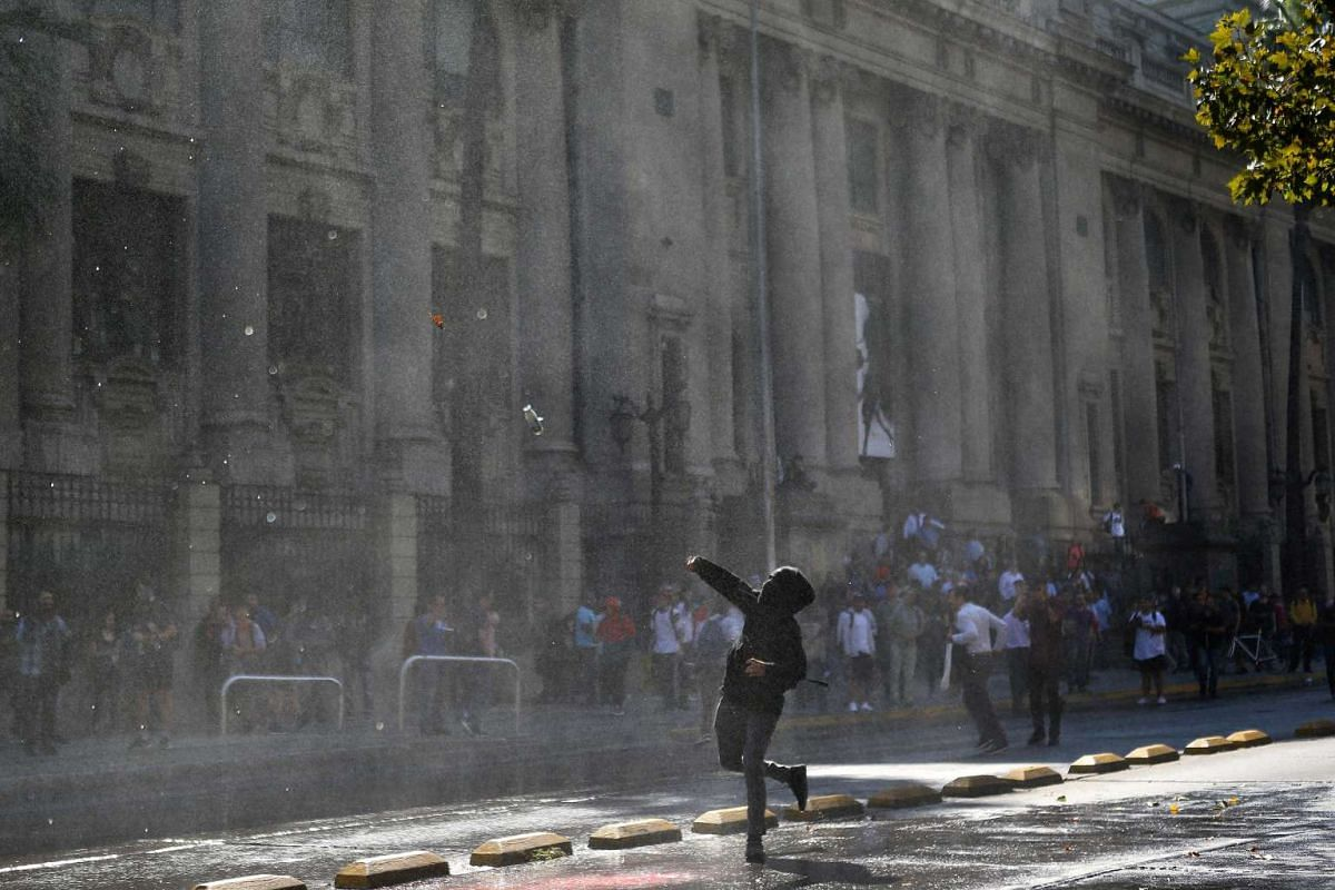 A demonstrator throws a bottle toward riot policemen during a protest calling for changes in the education system in Santiago, Chile April 11, 2017. PHOTO: REUTERS