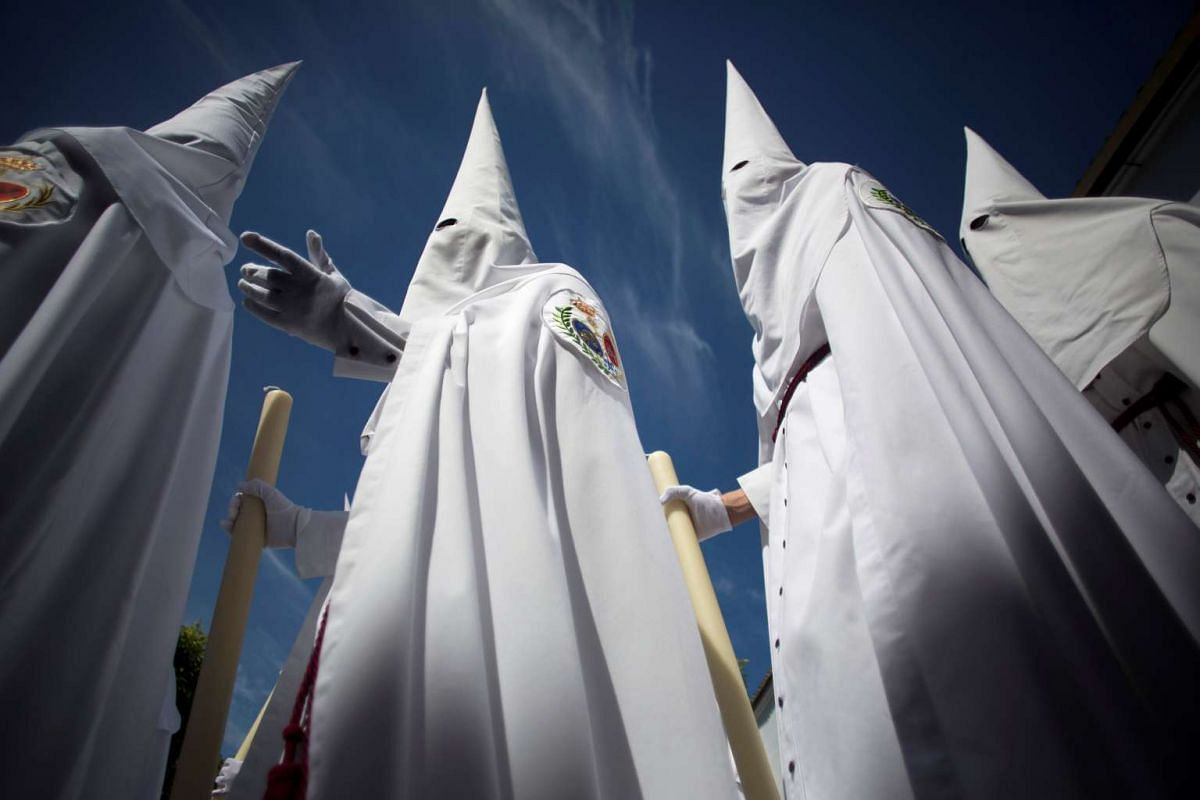 Penitents of La Paz (The Peace) brotherhood take part in a procession during Holy Week in the Andalusian capital of Seville, southern Spain, on April 9, 2017.