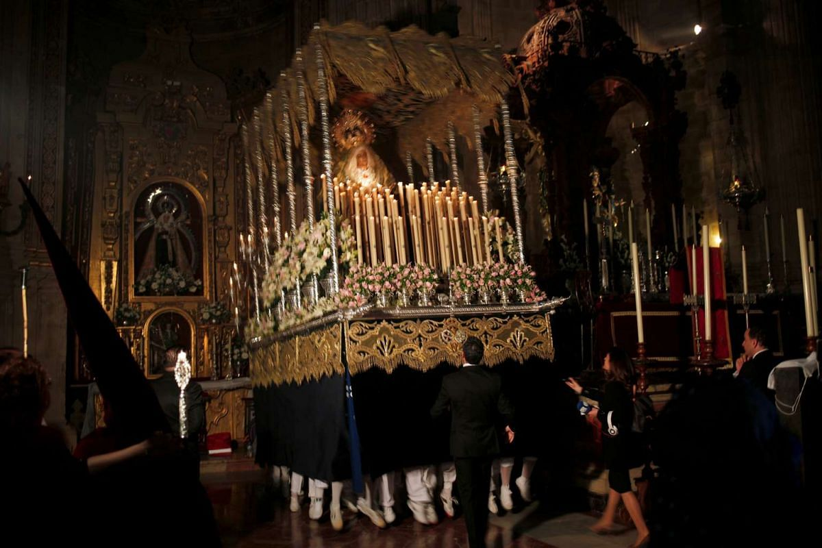"""Costaleros of the Los Gitanos brotherhood, known traditionally as """"paso"""", jump as they make the first """"levanta"""" inside a church in a procession during the Holy Week in Ronda, southern Spain, on April 9, 2017."""